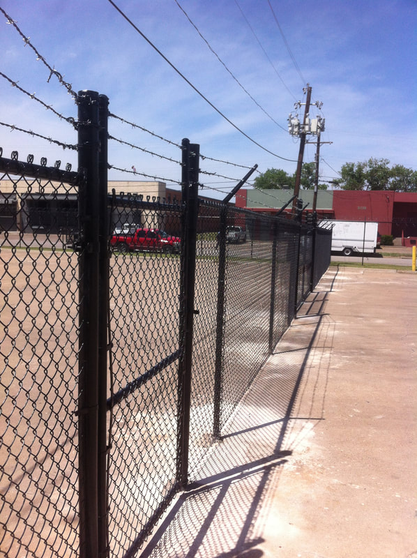 black chain link fence with barbed wire protecting a business