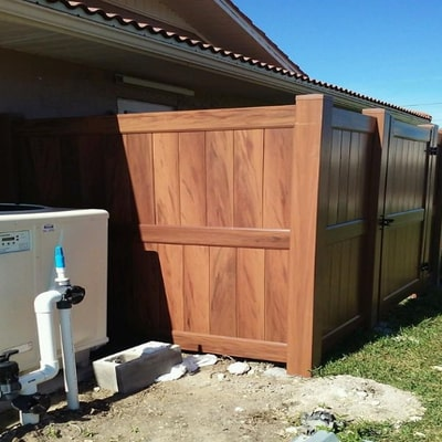 dark brown vinyl fence six feet tall around a suburban home