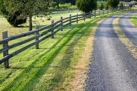 split rail cedar fence next to a gravel driveway